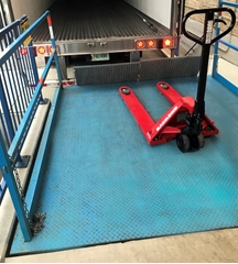 Loading dock scissors lift used to level the surface needed for loading and unloading trucks