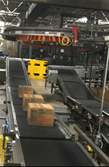 Two incline Motorized Driven Roller (MDR) zone to zone accumulation conveyors which move product from one warehouse ergonomic worker's elevation to the palletizer's infeed elevation.