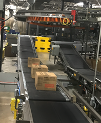 Boxes are being transported on zero pressure accumulation zoned conveyors; each individual box will not leave its own zone until the Motorized Driven Roller Conveyor (MDR) zone in front of it is clear of product.