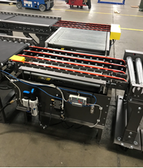 The box and tray transfer conveyor allows for line to line product transfer in a smaller footprint compared to bulky radius curve conveyors