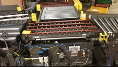 This conveyor transfer incorporates two sets of four-strand urethane drive bands which move product into lift position; the product is then is lifted up and down via pop up pneumatic rollers.